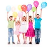 Pequeños niños lindos con el uo de las manos y los baloons Fotografía de archivo