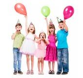 Pequeños niños lindos con el uo de las manos y los baloons Imágenes de archivo libres de regalías