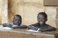 Pequeños niños lindos que aprenden con las plumas y el papel en África Sch Foto de archivo