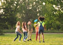 Pequeños niños lindos que juegan con el disco volador al aire libre imágenes de archivo libres de regalías