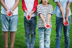 Pequeños niños lindos que llevan a cabo corazones rojos mientras que se coloca en hierba verde Imagen de archivo libre de regalías