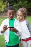 Pequeños niños lindos que miran smartphone Foto de archivo libre de regalías