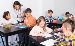 Pequeños niños positivos con el dibujo del profesor en sala de clase foto de archivo libre de regalías