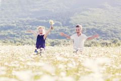 Pequeños niños preciosos en el campo de margaritas fotos de archivo