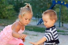 Pequeños niños preciosos que juegan en la salvadera Foto de archivo libre de regalías