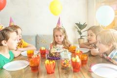 Pequeños niños que celebran cumpleaños junto en casa Imágenes de archivo libres de regalías