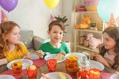 Pequeños niños que celebran cumpleaños junto en casa Foto de archivo
