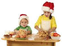 Pequeños niños que cocinan la torta de la Navidad Fotografía de archivo libre de regalías