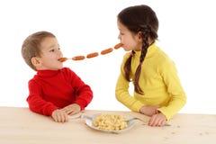 Pequeños niños que comparten el encadenamiento de salchichas Imagen de archivo libre de regalías