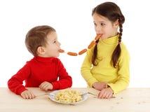 Pequeños niños que comparten el encadenamiento de salchichas Foto de archivo libre de regalías