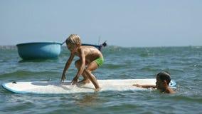 Pequeños niños que disfrutan de las manos surfboarding y que agitan del mar en la cámara lenta almacen de metraje de vídeo