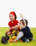 Pequeños niños que juegan con el conejito de pascua Fotografía de archivo