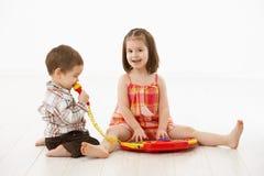 Pequeños niños que juegan con el instrumento del juguete Fotos de archivo