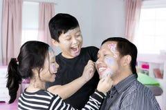 Pequeños niños que juegan con el padre en el dormitorio Foto de archivo