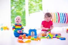 Pequeños niños que juegan con los coches del juguete imagenes de archivo