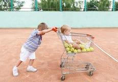 Pequeños niños que juegan en un patio del tenis con la carretilla que hace compras imagen de archivo