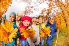 Pequeños niños sonrientes en parque con las hojas amarillas Imagenes de archivo