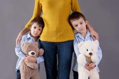 Pequeños niños tristes, muchachos, abrazando a su madre en casa, aislante Fotos de archivo