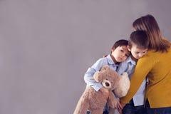 Pequeños niños tristes, muchachos, abrazando a su madre en casa, aislante Imagenes de archivo