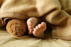 Pequeños pies del bebé debajo de una manta caliente Imagenes de archivo