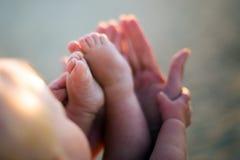 Pequeños pies del bebé en las manos de las madres al aire libre en el backligh Fotos de archivo