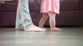 Pequeños pies del bebé que caminan en piso con la ayuda del padre Pasos de los pies del niño en casa almacen de metraje de vídeo
