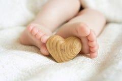 Pequeños pequeños pies delicados para guardar el corazón de madera Foto de archivo libre de regalías