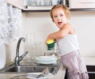 Pequeños platos de la limpieza de la muchacha Imagen de archivo