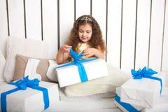 Pequeños regalos abiertos sonrientes de la niña pequeña Foto de archivo libre de regalías