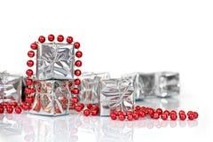 Pequeños regalos de la Navidad en papel de plata brillante y el ornamento rojo de las gotas de la malla Imagen de archivo libre de regalías