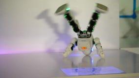 Pequeños robots del cyborg, humanoids con la cara y danzas del cuerpo a la música almacen de video