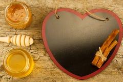 Pequeños tarros de miel fresca con el drizzler, canela en el fondo de madera, visión superior Foto de archivo libre de regalías