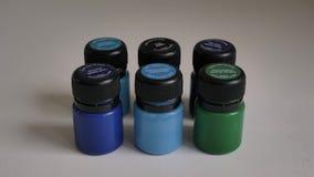 Pequeños tarros del soporte de la pintura de la tela en la superficie blanca almacen de metraje de vídeo