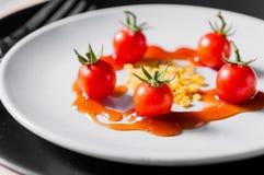 Pequeños tomate y habas en el plato blanco de la bio comida elegante Fotos de archivo libres de regalías