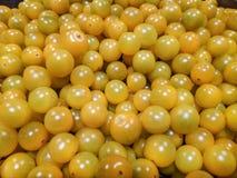 Pequeños tomates amarillos en fondo del uniforme del bulto fotos de archivo