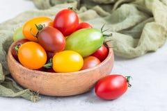 Pequeños tomates de cereza coloridos en cuenco de madera en la tabla, horizontal Foto de archivo