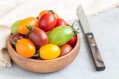 Pequeños tomates de cereza coloridos en el cuenco de madera, preparado, horizontal Imágenes de archivo libres de regalías