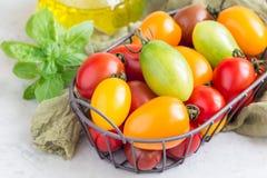 Pequeños tomates de cereza coloridos en la cesta del metal, horizontal Foto de archivo libre de regalías