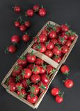 Pequeños tomates de cereza rojos en una cesta de mimbre de la rota en un fondo negro de madera en el estilo rústico, foco selecti foto de archivo libre de regalías