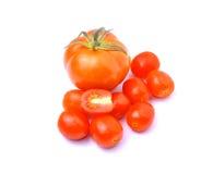 Pequeños tomates de los tomates grandes en el fondo blanco Imagenes de archivo