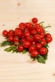 Pequeños tomates e hierbas frescas en fondo de madera Fotos de archivo