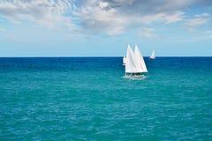 Pequeños veleros que navegan en las aguas tranquilas del mar adriático Italia del sur Imagen de archivo libre de regalías
