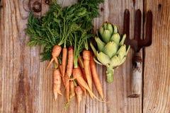 Pequeños zanahorias, alcachofa y rastrillo en una tabla de madera vieja Fotografía de archivo libre de regalías