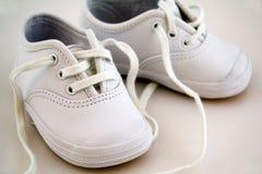 Pequeños zapatos de bebé blancos Imagen de archivo libre de regalías