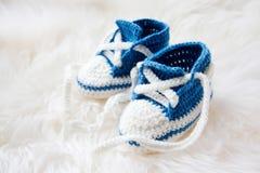 Pequeños zapatos de bebé Primeras zapatillas de deporte tejidas a mano para el muchacho recién nacido Fotografía de archivo libre de regalías