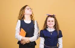 Peque?as muchachas con la carpeta del papel cuaderno para las notas del diario lecci?n del estudio Conocimiento y educaci?n De nu imagenes de archivo