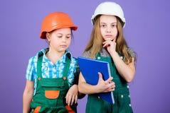 peque?as muchachas que reparan junto en taller Inspector del capataz reparaci?n Ni?os en casco con la tableta y el rodillo imagen de archivo