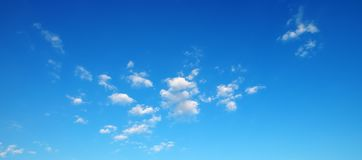 Peque?as nubes mullidas en el cielo azul brillante foto de archivo libre de regalías