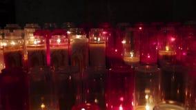 Peque?as velas en iglesia Filas de velas ardientes en una iglesia oscuro Peque?as velas que encienden en iglesia cat?lica en oscu metrajes