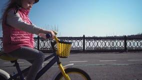 Peque?a bici rubia de cinco a?os del montar a caballo de la muchacha en un parque viejo almacen de video